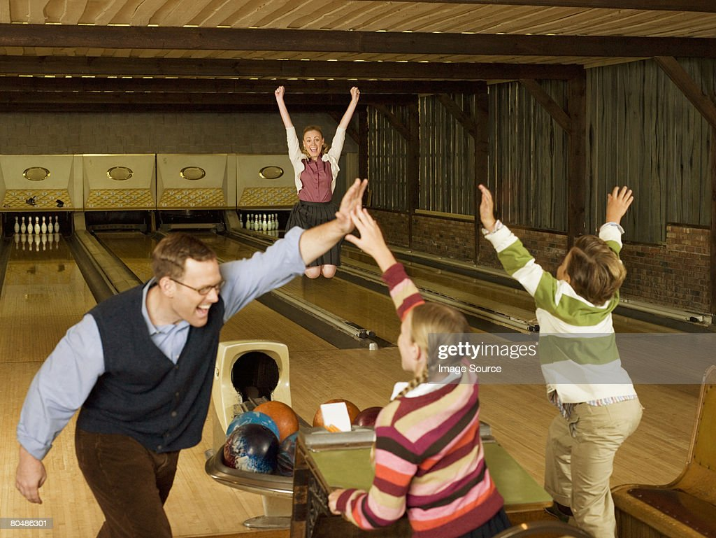Happy family at bowling alley : Stock Photo