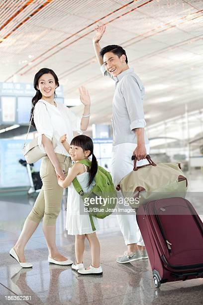 Happy family at the airport waving goodbye