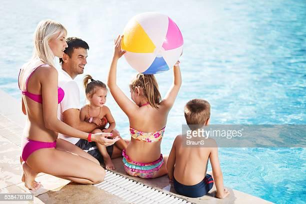 Famille heureuse au bord de la piscine.