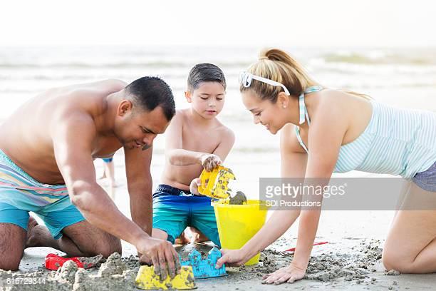 Happy family builds sand castle