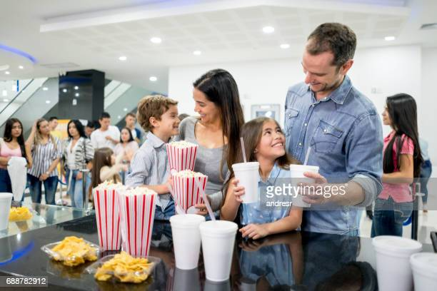 Happy family buying popcorn and drinks at the cinema