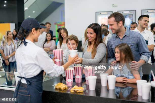 Happy family buying popcorn and drinks at the movies