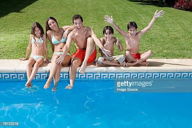 Famille heureuse au bord de la piscine