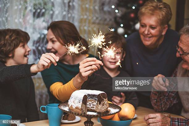 Happy family celebrate Christmas Eve with sparkles