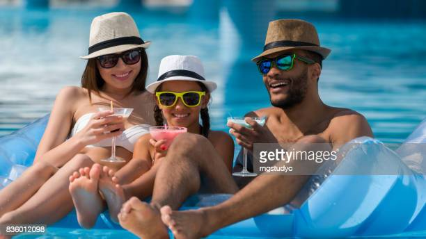Happy family drinking coktail  in swimming pool