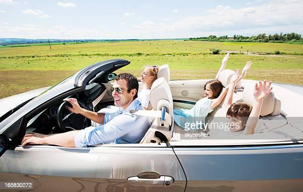 Heureuse famille de conduire une voiture décapotable dans une voiture.