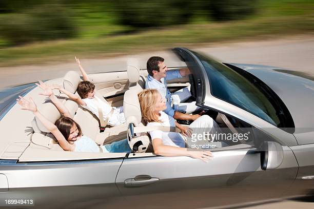 Happy family driving in a convertible car
