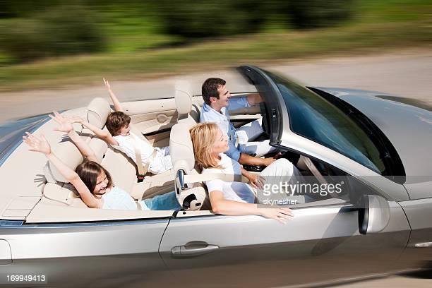Heureuse famille de conduire une voiture décapotable