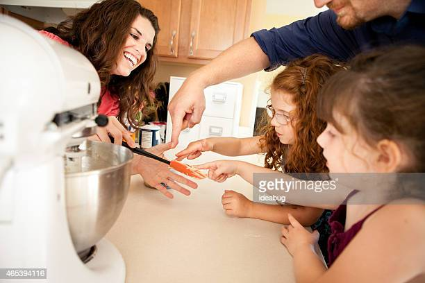Happy Family Eating Cookie Dough in Kitchen while Baking Together