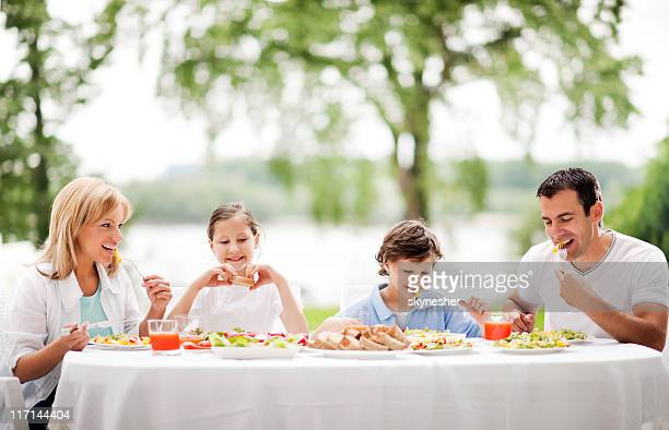 Happy family eating together outdoor.