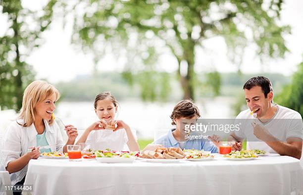 Heureuse famille manger ensemble à l'extérieur.