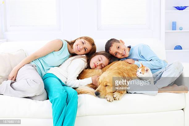 Happy family embracing sleeping dog and cat.