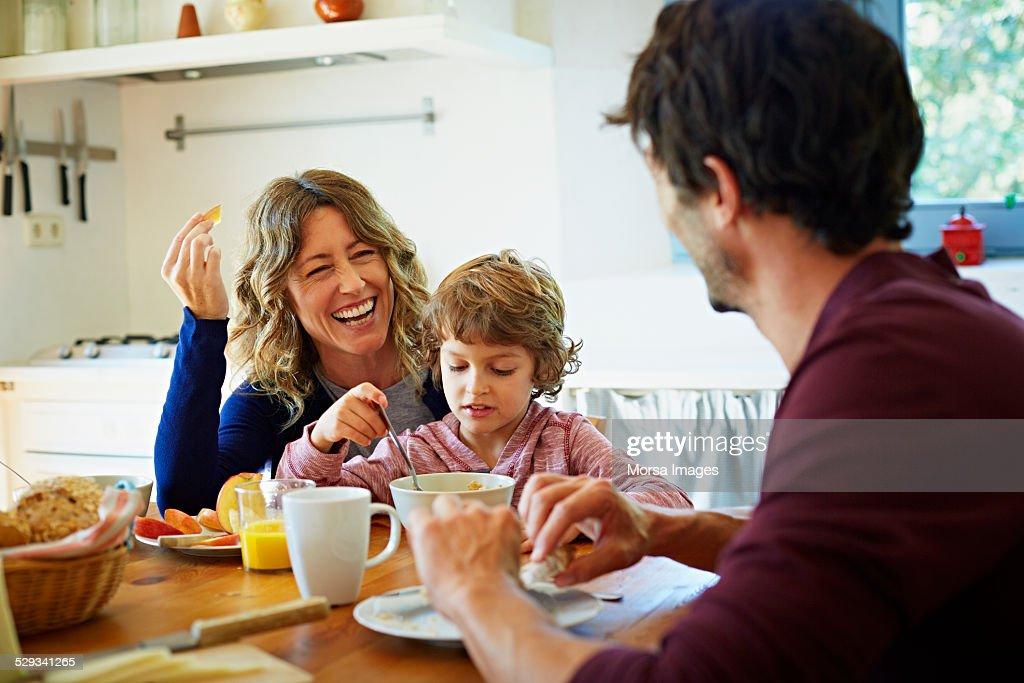 Happy family enjoying breakfast at table : Stock Photo