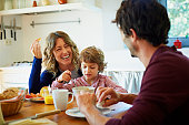 Happy family enjoying breakfast at table