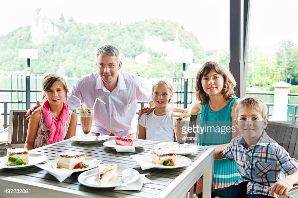 Happy family enjoying ice cream sundae and pastry