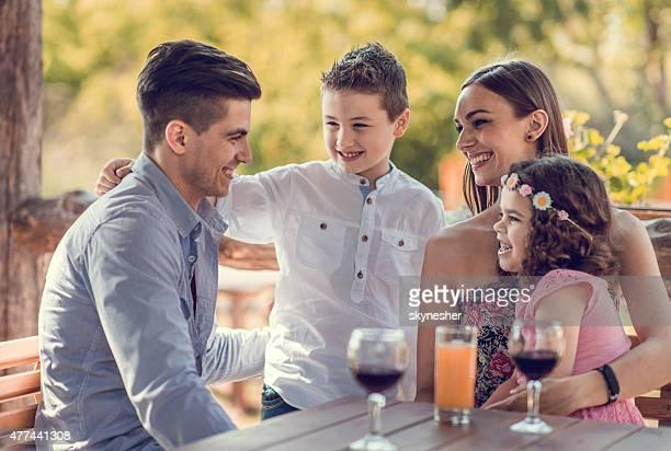 Feliz família desfrutar de café e a dialogar.