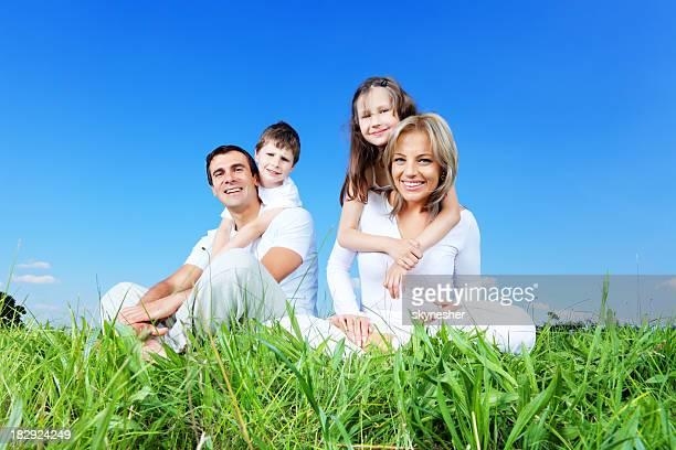 Happy family enjoying outdoor, sitting on green grass.