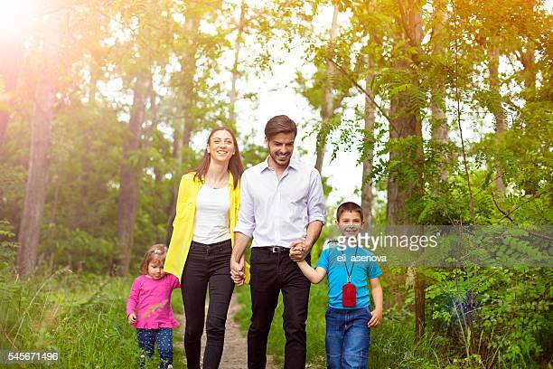 Happy family enjoying their summer day walk in nature.