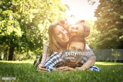 Happy family enjoying together in summer day. Family lying on grass. Mother and daughter lying on father piggyback. : Stock Photo