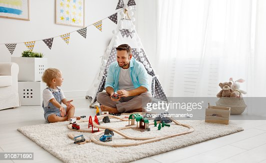 happy family father and child son playing   in toy railway in playroom : Stock Photo