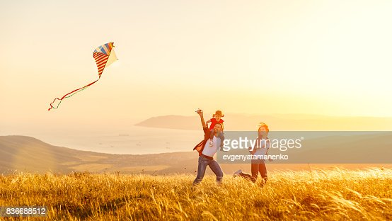 Happy family father of mother and child daughter launch a kite on nature at sunset : Foto stock