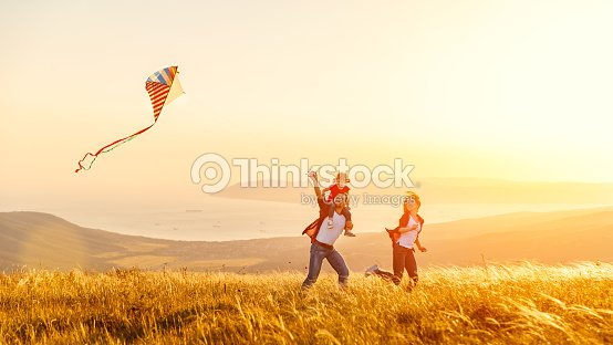 Happy family father of mother and child daughter launch a kite on nature at sunset : Stock Photo