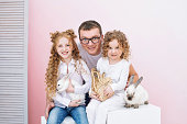 Happy family father, two daughters and fluffy animals beautiful rabbits with smiles on pink background