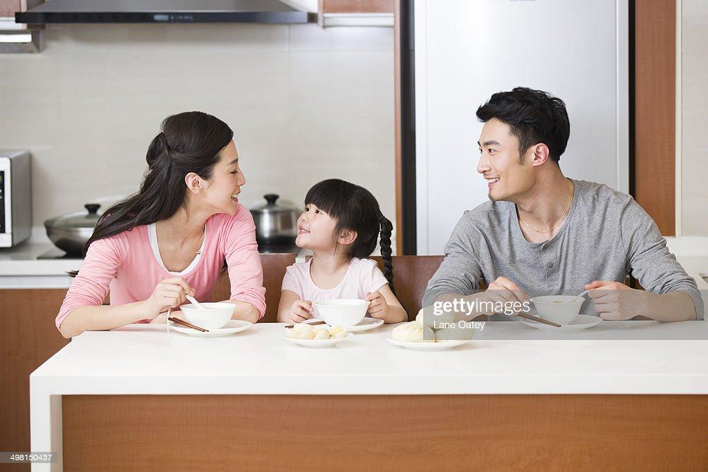 Happy family having breakfast : Stock Photo