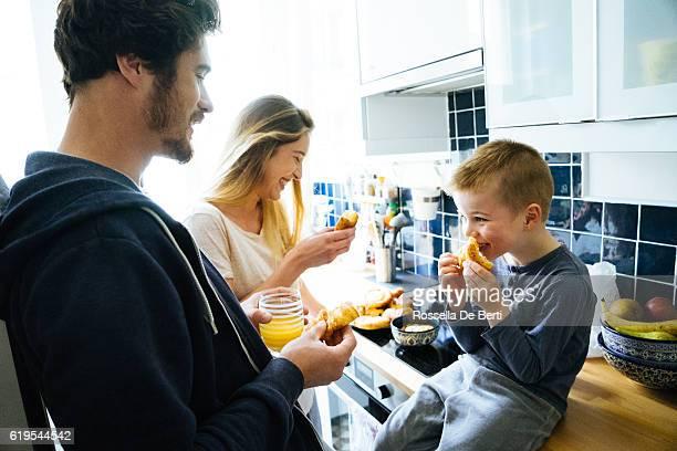 Heureuse famille petit déjeuner ensemble dans la cuisine
