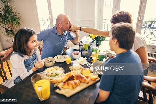 Happy Family Having Breakfast together, man kissing wife