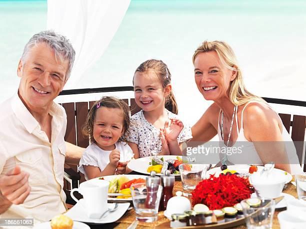 Happy family having exotic beach dinner