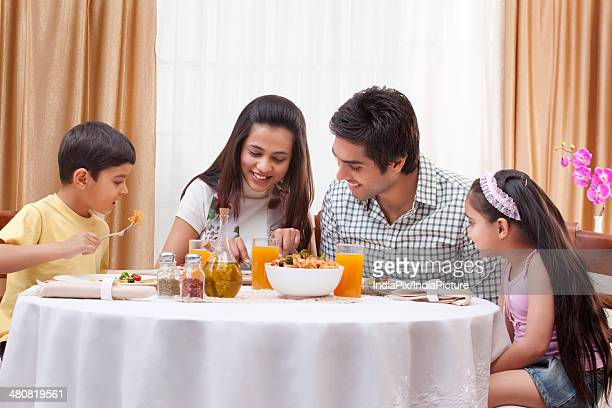 Happy family having food together at restaurant table