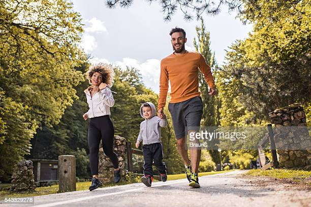 Happy family having fun while running in the park.