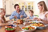 Happy family having roast chicken dinner at dining table
