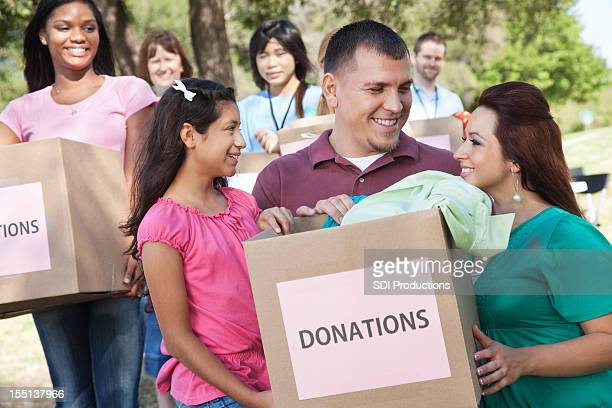 Happy family holding donations box at a donation center