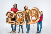 Happy family holding golden 2019 sign balloons for new year and looking at camera isolated on white