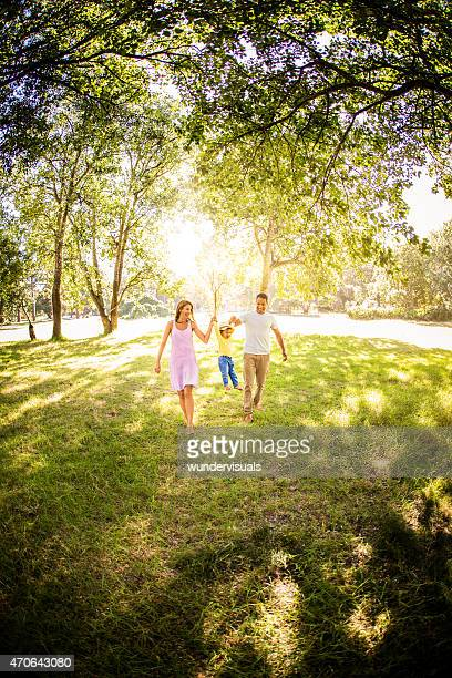 Happy family holding hands while walking and swinging their todd