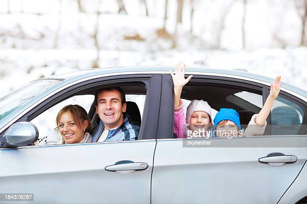 A happy family in a car against a snowy backdrop