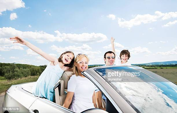 Happy family in a convertible car.