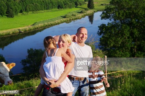 Happy family in front of lake : Stock Photo