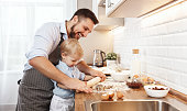 happy family in kitchen. mother and child son baking cookies together