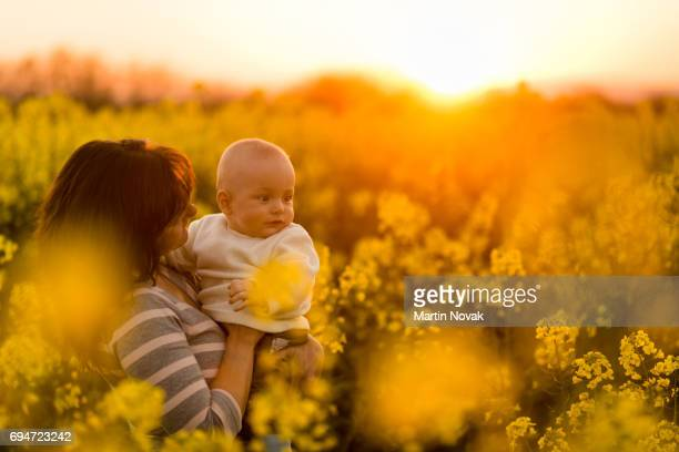 Happy family in rapeseed field. Mother with baby boy.