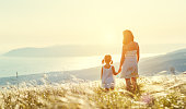 Happy family in summer outdoors. Mother and child daughter stand with their backs and admire sunset