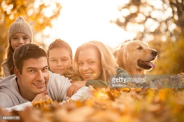 Glückliche Familie im Herbst park mit Hund