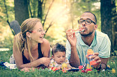 Happy interracial family is blowing bubbles  in retro filter effect or instagram filter. Mixed diverse family is enjoying a day in the park. Mother father and mulatto son are smiling and are picnickin