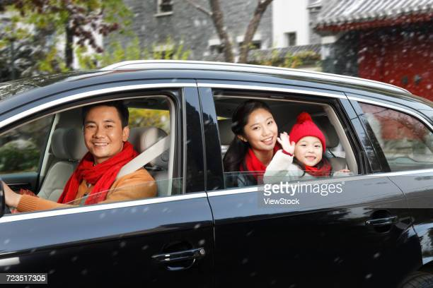 A happy family is sitting in a car.