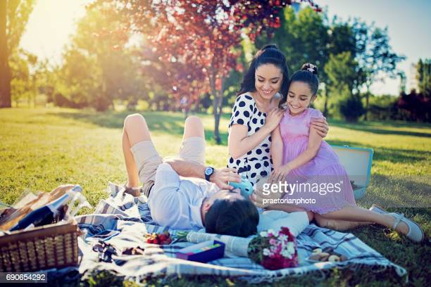 Happy family is taking photos at picnic in the park