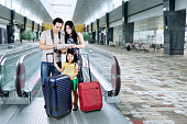 Asian family doing holiday trip and looking a map on the digital tablet at the airport hall
