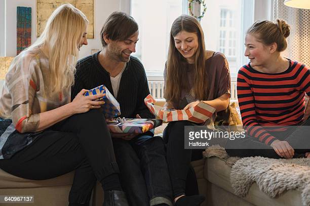 Happy family looking at daughter opening birthday present in living room