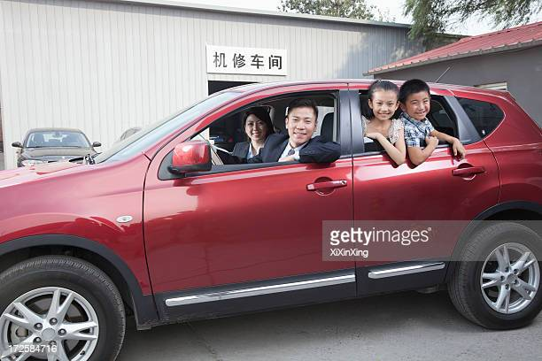 Happy Family Looking Out of a Car